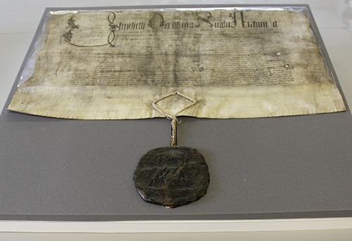 Parchment document with black writing, very faded. It has a green wax seal at the bottom suspended on a length of cord.