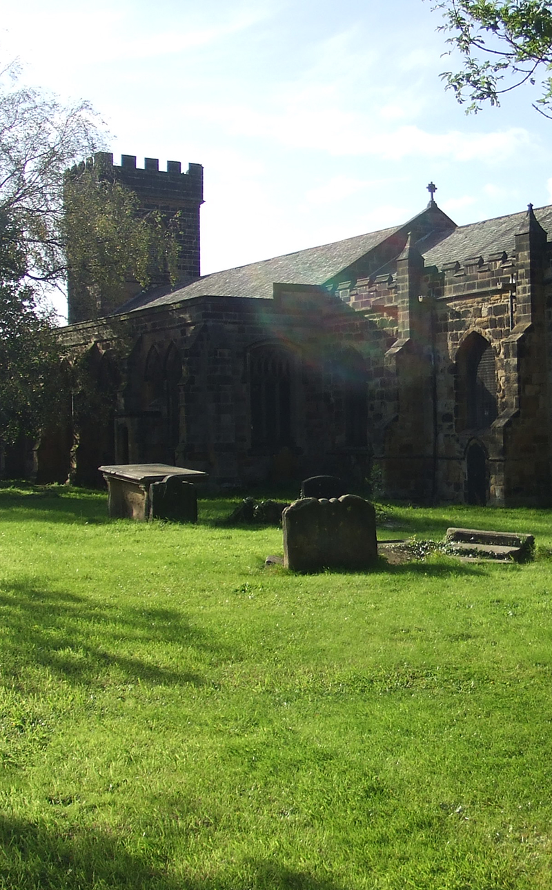 Colour photograph of a medieval church in a churchyard with gravestones.