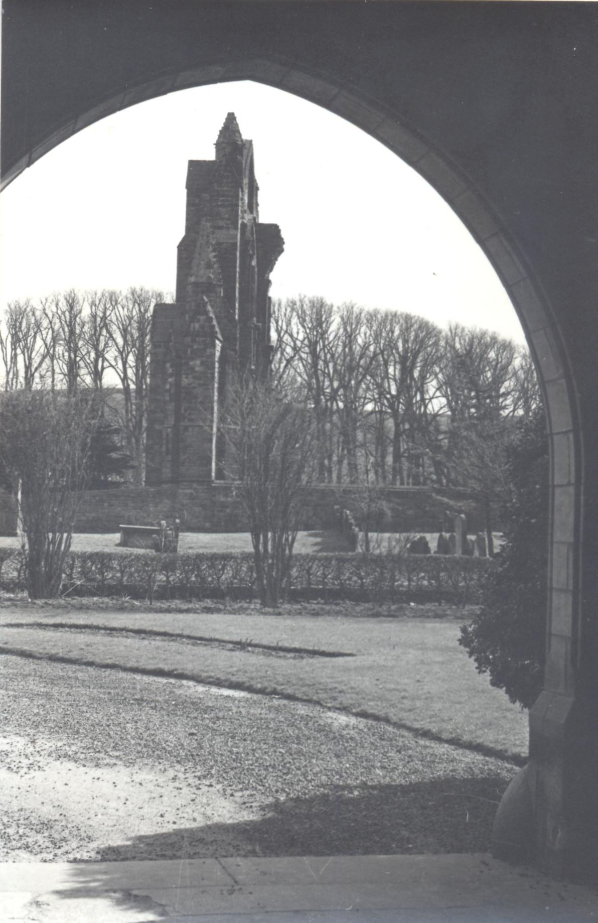 Black and white photograph. The ruins of the east end of a priory church viewed through a stone and terracotta arch with a garden and then a graveyard in between.