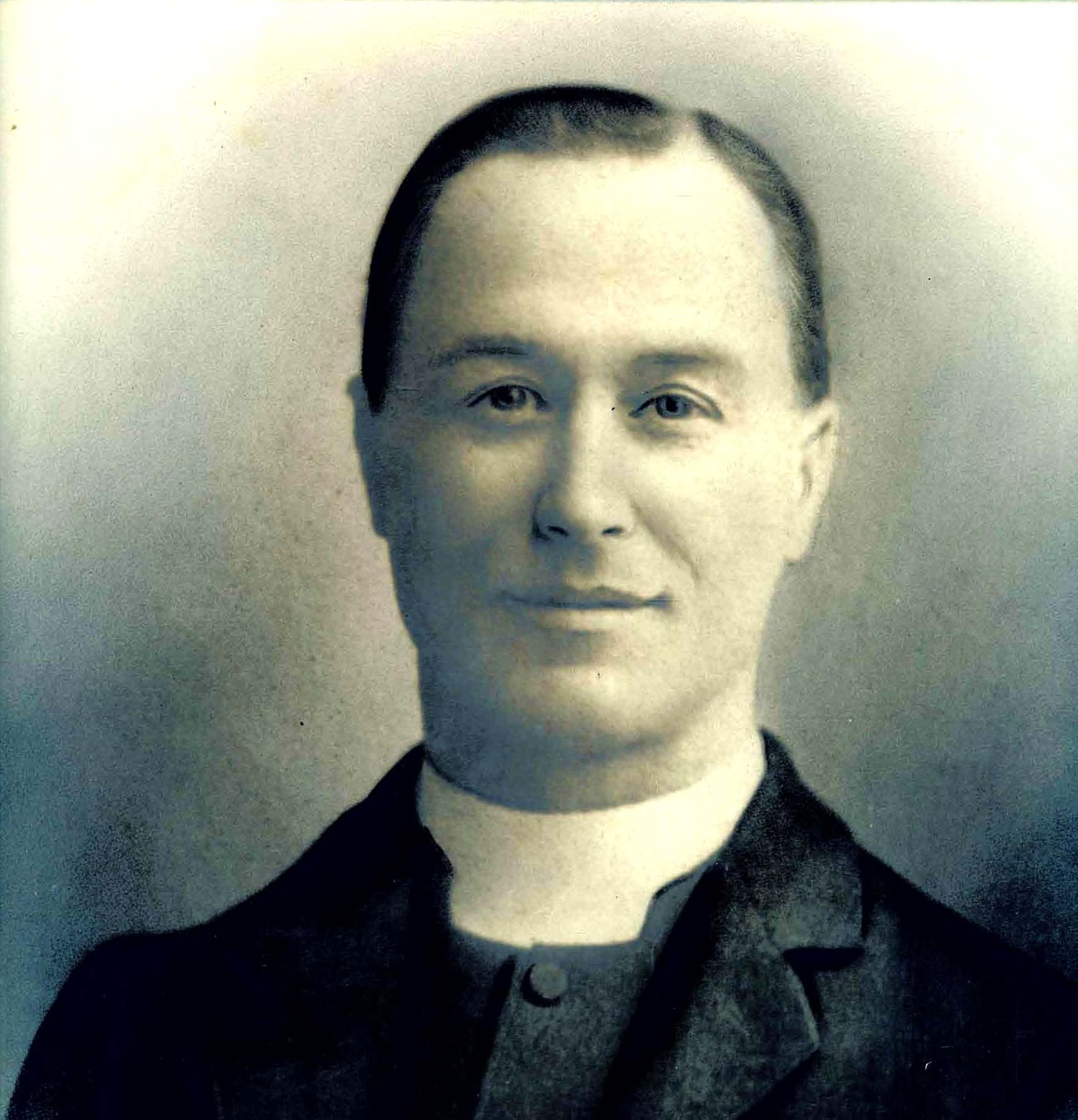 Black and white photograph of a white man in his middle years wearing a cleric's dog collar.