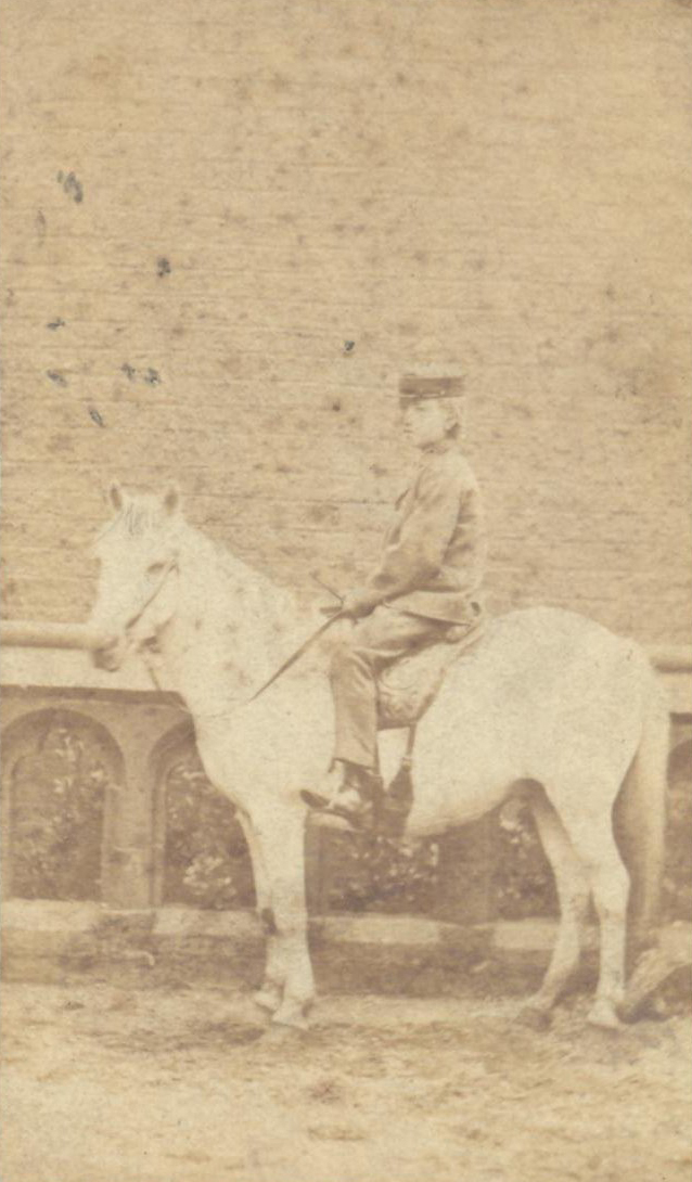 A sepia photo from the 1860s of a schoolboy sitting on a pony in front of a wall.