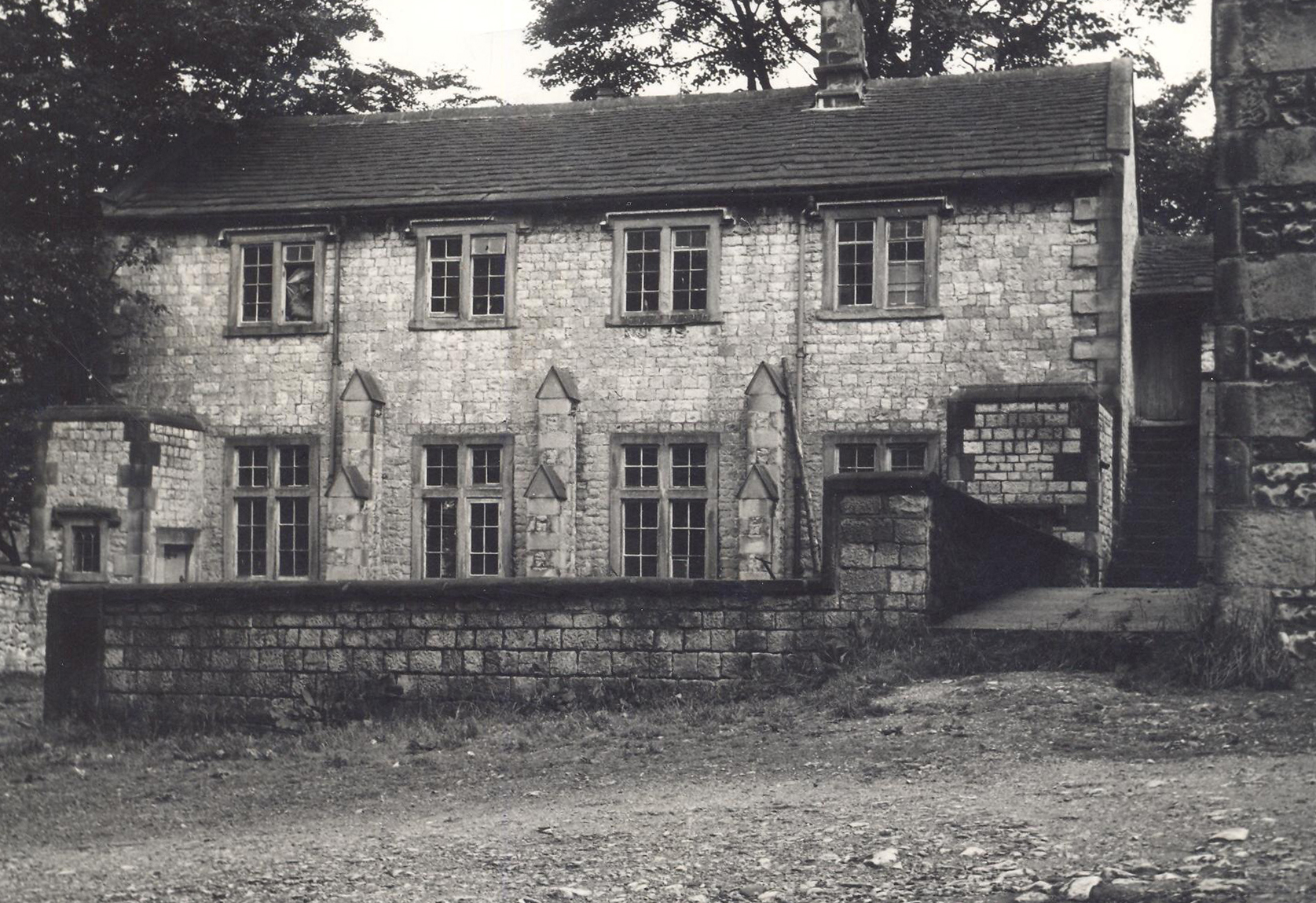 Black and white photograph of the Old Grammar School Tideswell, a two storey stone building with square-headed windows.